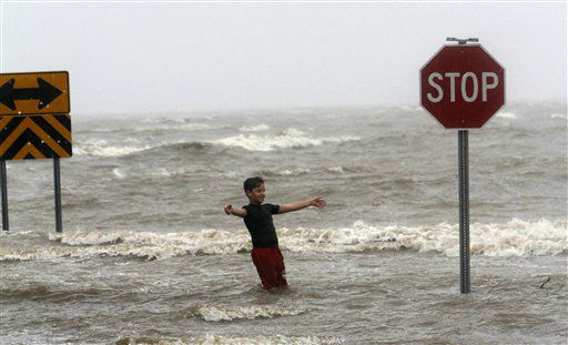 Landon Gazzier leans into the wind as the waves crash over the sea wall in Bayou La Batre on Wednesday, August 29, 2012.  Hurricane Isaac has dumped more than five inches of rain on the Alabama coast and knocked out power to some residents, but it hasn&#39;t interrupted the everyday life of others.  Residents of Dauphin Island lost power, but they also escaped the worst of Isaac. The weather service reports wind gusts of 47 mph.   <span class=meta>(AP Photo&#47; Butch Dill)</span>
