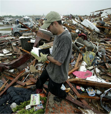 "<div class=""meta image-caption""><div class=""origin-logo origin-image ""><span></span></div><span class=""caption-text"">Justin Stehan salvages photographs from his tornado-ravaged home Tuesday, May 21, 2013, in Moore, Okla. A huge tornado roared through the Oklahoma City suburb Monday, flattening entire neighborhoods and destroying an elementary school with a direct blow as children and teachers huddled against winds.   (AP Photo/ Charlie Riedel)</span></div>"