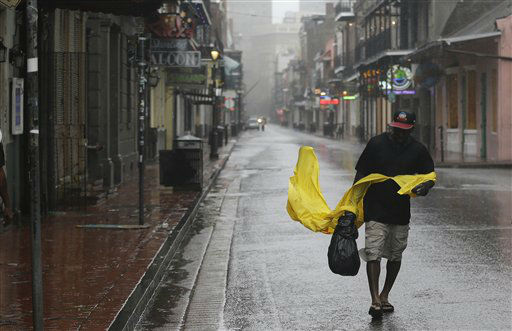 "<div class=""meta ""><span class=""caption-text "">A man struggles with his rain cover as he walks up Bourbon Street in the French Quarter as Hurricane Isaac makes landfall, Wednesday, Aug. 29, 2012, in New Orleans, La.  Isaac was packing 80 mph winds, making it a Category 1 hurricane. It came ashore early Tuesday near the mouth of the Mississippi River, driving a wall of water nearly 11 feet high inland and soaking a neck of land that stretches into the Gulf.   (AP Photo/ Eric Gay)</span></div>"