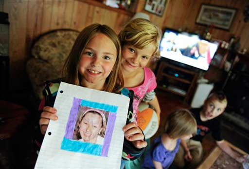 Christina Milton, 8, left, shows a piece of artwork she made from a photo of her cousin, Amanda Berry, that she cut out of a missing person poster in Elizabethton, Tenn., on Wednesday, May 8, 2013. Another cousin, Haley Berry, 9, looks over her shoulder. Amanda Berry is one of three women who were rescued from a Cleveland home on Monday after they went missing separately about a decade ago, when they were in their teens or early 20s. &#40;AP Photo&#47;Patrick Murphey-Racey&#41; <span class=meta>(AP Photo&#47; Patrick Murphy-Racey)</span>