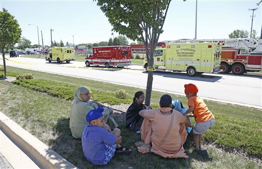 Bystanders sit in the shade at the scene of a shooting inside The Sikh Temple in Oak Creek, Wis, Sunday, Aug 5, 2012. Greenfield Police Chief Bradley Wentlandt says tactical officers have been through the temple where shots were fired about 10:30 a.m. Sunday. He says they found four people inside the building and three people outside.   <span class=meta>(AP Photo&#47; JEFFREY PHELPS)</span>