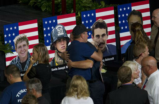 Photos of some of the 19 fallen firefighters line the front of the stage before a memorial service for the 19 fallen firefighters at Tim&#39;s Toyota Center in Prescott Valley, Ariz. on Tuesday, July 9, 2013.   Prescott&#39;s Granite Mountain Hotshots were overrun by smoke and fire while battling a blaze on a ridge in Yarnell, about 80 miles northwest of Phoenix on June 30, 2013.    <span class=meta>(AP Photo&#47; MICHAEL CHOW)</span>