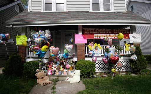 The front porch of Amanda Berry&#39;s home is decorated with balloons and signs on Wednesday, May 8, 2013, in Cleveland. Berry, 27, Michelle Knight, 32, and Gina DeJesus, had apparently been held captive in a house since their teens or early 20s, police said. &#40;AP Photo&#47;Tony Dejak&#41; <span class=meta>(AP Photo&#47;Tony Dejak)</span>