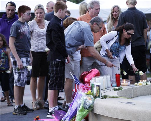 "<div class=""meta ""><span class=""caption-text "">Family members of the victims of Friday's mass shooting in Aurora, Colo., leave roses at a memorial as they leave a prayer vigil, Sunday, July 22, 2012, in Aurora, Colo. 12 people were killed and 58 were injured in a shooting during an early Friday premiere of ?The Dark Knight Rises."" (AP Photo/Ted S. Warren) (AP Photo/ Ted S. Warren)</span></div>"