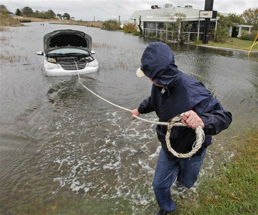 "<div class=""meta ""><span class=""caption-text "">Glenn Heartley pulls on a rope attached to his car in preparation for getting it towed from a creek in Chincoteague, Va., Tuesday, Oct. 30, 2012. Heartley and his wife were swept off the road into the shallow creek during superstorm Sandy's arrival Monday. (AP Photo/Steve Helber) (AP Photo/ Steve Helber)</span></div>"