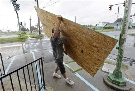 John Taylor carries a piece of plywood to board up store windows Tuesday, Aug. 28, 2012, in Chalemette, La. The U.S. National Hurricane Center in Miami said Isaac became a Category 1 hurricane Tuesday with winds of 75 mph. It could get stronger by the time it&#39;s expected to reach the swampy coast of southeast Louisiana.   <span class=meta>(AP Photo&#47; David J. Phillip)</span>
