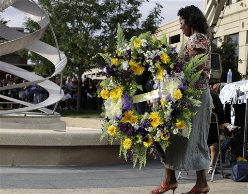 A woman carries a wreath, Sunday, July 22, 2012, in Aurora, Colo., during a prayer vigil for the victims of Friday&#39;s mass shooting at a movie theater. Twelve people were killed and dozens were injured in a shooting attack Friday at the packed theater during a showing of the Batman movie, &#34;The Dark Knight Rises.&#34; Police have identified the suspected shooter as James Holmes, 24. &#40;AP Photo&#47;Ted S. Warren&#41; <span class=meta>(AP Photo&#47; Ted S. Warren)</span>