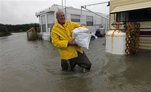 "<div class=""meta ""><span class=""caption-text "">Terry Robinson wades through water after retrieving some of his belongings from his flooded trailer at RV Park in Kitty Hawk, N.C., Monday, Oct. 29, 2012. Flooding from Hurricane Sandy left many roads impassable while localized flooding from a storm surge forced some people from their homes. (AP Photo/Gerry Broome) (AP Photo/ Gerry Broome)</span></div>"
