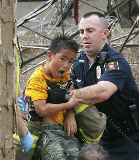 A boy is pulled from beneath a collapsed wall at the Plaza Towers Elementary School following a tornado in Moore, Okla., Monday, May 20, 2013. A tornado as much as a mile &#40;1.6 kilometer&#41; wide with winds up to 200 mph &#40;320 kph&#41; roared through the Oklahoma City suburbs Monday, flattening entire neighborhoods, setting buildings on fire and landing a direct blow on the elementary school. &#40;AP Photo Sue Ogrocki&#41; <span class=meta>(AP Photo&#47; Sue Ogrocki)</span>