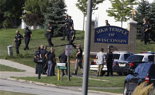 Police personnel walk near the sign outside the Sikh Temple of Wisconsin in Oak Creek, Wis., after a shooting Sunday, Aug 5, 2012. A gunman killed six people at the suburban Milwaukee temple in a rampage that left terrified congregants hiding in closets and others texting friends outside for help. The suspect was killed outside the temple in a shootout with police officers.   <span class=meta>(AP Photo&#47; JEFFREY PHELPS)</span>