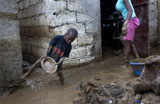 Winsky Pierre, left, 5, helps to drain mud from his flooded house after the passing of Tropical Storm Isaac in Port-au-Prince, Haiti, Sunday Aug. 26, 2012. The death toll in Haiti from Tropical Storm Isaac has climbed to seven after an initial report of four deaths, the Haitian government said Sunday.  <span class=meta>(AP Photo&#47; Dieu Nalio Chery)</span>