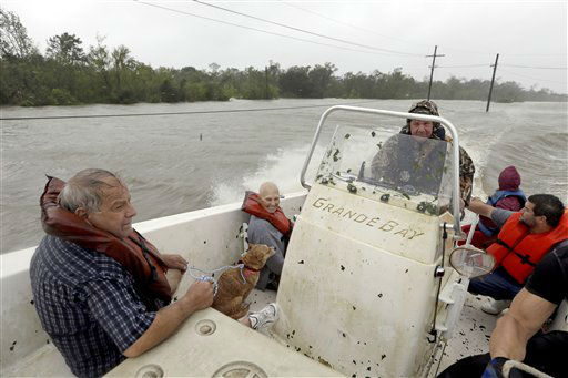 Lanny LaFrance, center, drives his boat while rescuing Carlo Maltese, left, his wife Elaine, bottom center, and son Sam, right, from their flooded home as Hurricane Isaac hits Wednesday, Aug. 29, 2012, in Braithwaite, La.   <span class=meta>(AP Photo&#47; David J. Phillip)</span>