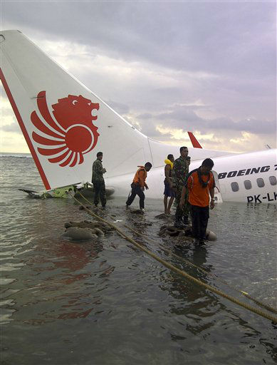 "<div class=""meta ""><span class=""caption-text "">In this photo released by Indonesia's National Rescue Team, rescuers stand near the wreckage of a crashed Lion Air plane in Bali, Indonesia on Saturday, April 13, 2013. The plane carrying more than 100 passengers and crew overshot a runway on the Indonesian resort island of Bali on Saturday and crashed into the sea, injuring nearly two dozen people, officials said.  (AP Photo/ Uncredited)</span></div>"