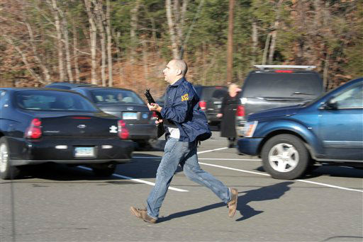 In this photo provided by the Newtown Bee, a state police officer runs outside of Sandy Hook Elementary School in Newtown, Conn., where authorities say a gunman opened fire, killing 26 people, including 20 children, Friday, Dec. 14, 2012. &#40;AP Photo&#47;Newtown Bee, Shannon Hicks&#41;   <span class=meta>(AP Photo&#47; Shannon Hicks)</span>