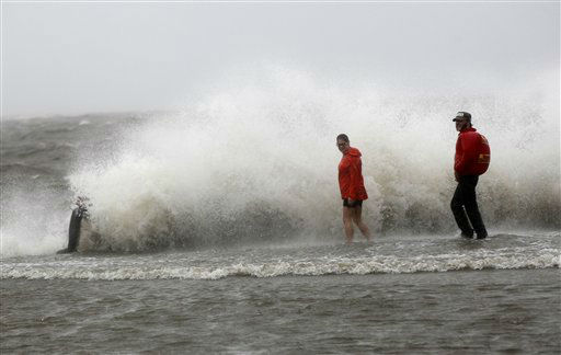 A man sits on the seawall as his friends walk in the storm surge from Isaac, on Lakeshore Drive along Lake Pontchartrain, as the storm approaches landfall, in New Orleans, Tuesday, Aug. 28, 2012.   <span class=meta>(AP Photo&#47; Gerald Herbert)</span>