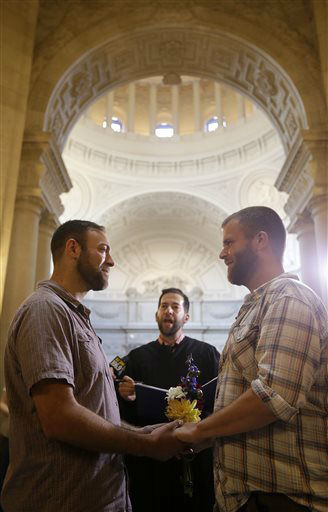 Craig Stein, left, holds hands with Bobby Meadows as they get married, officiated by marriage commissioner Jared Scherer, at City Hall in San Francisco, Friday, June 28, 2013. A three-judge panel of the 9th U.S. Circuit Court of Appeals issued a brief order Friday afternoon dissolving, &#34;effective immediately,&#34; a stay it imposed on gay marriages while the lawsuit challenging the ban advanced through the court.  <span class=meta>(AP Photo&#47; Jeff Chiu)</span>