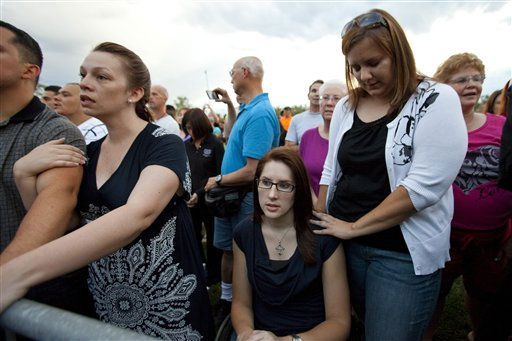 Anne Marie Hochhalter, 30, bottom, and her friend Roxy Chesser, 30, second from right, attend a prayer vigil, held to remember the lost and injured in Friday&#39;s mass shooting at a movie theater, in a park outside the Aurora Municipal Center in Aurora, Colo., Sunday July 22, 2012. Hochhalter, a paralyzed victim of the Columbine High School tragedy over 12 years ago, and other survivors of the 1999 massacre reached out to people who survived the theater shooting. Twelve people were killed and dozens were injured in a shooting attack during a showing of the Batman movie, &#34;The Dark Knight Rises.&#34; Police have identified the suspected shooter as James Holmes. &#40;AP Photo&#47;Barry Gutierrez&#41; <span class=meta>(AP Photo&#47; Barry Gutierrez)</span>