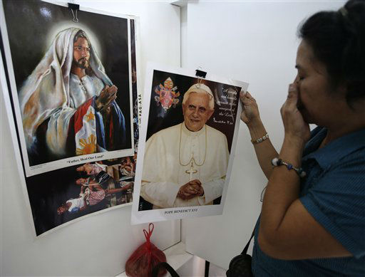 Filipino Roman Catholic devotee Betty Abainza shops for posters of resigning Pope Benedict XVI at a religious store in Manila, Philippines Thursday Feb. 28, 2013. Pope Benedict XVI formally resigns Thursday, the first pope to abdicate the papacy in 600 years. <span class=meta>(AP photo)</span>