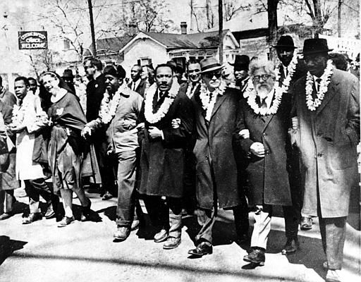 Dr. Martin Luther King Jr. links arms with other civil rights leaders as they begin the march to the state capitol in Montgomery from Selma, Ala. on March 21, 1965. The demonstrators are marching for voter registration rights for blacks. Accompanying Dr. Martin Luther King Jr. &#40;fourth from right&#41;, are on his left Ralph Bunche, undersecretary of the United Nations, Rabbi Abraham Joshua Heschel, and Rev. Fred Shuttlesworth. They are wearing leis given by a Hawaiian group.  &#40;AP Photo&#41; <span class=meta>(AP Photo&#47; XNBG)</span>