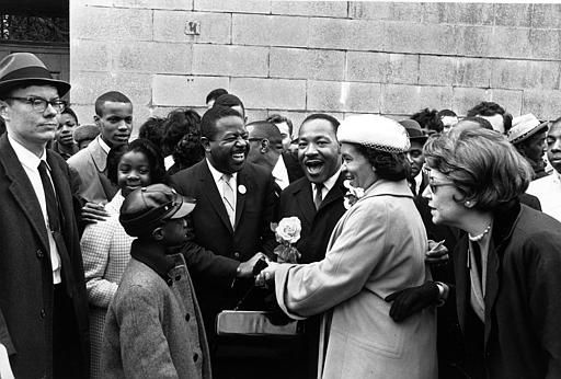 "<div class=""meta ""><span class=""caption-text "">Dr. Martin Luther King Jr., center, is presented a large rose by Mrs. Virgil Wood, right, who is shaking hands with King's aide Rev. Ralph Abernathy outside the Patrick Campbell School in Roxbury section of Boston, Mass., April 22, 1965.  King, who is in Boston to lead a civil rights march Friday, toured schools and housing in the Roxbury section before addressing a joint session of the Massachusettts Legislature later in the afternoon.  (AP Photo) (AP Photo/ XNBG)</span></div>"