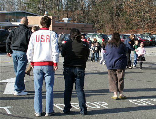 In this photo provided by the Newtown Bee, people look on as students are led out of Sandy Hook Elementary School in Newtown, Conn., where authorities say a gunman opened fire, killing 26 people, including 20 children, Friday, Dec. 14, 2012. &#40;AP Photo&#47;Newtown Bee, Shannon Hicks&#41;   <span class=meta>(AP Photo&#47; Shannon Hicks)</span>