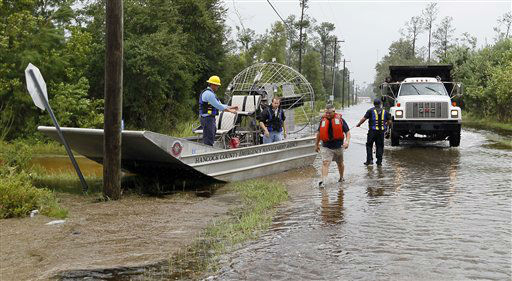 First responders seek the assistance of a City of Bay St. Louis, Miss., dump truck to tow their airboat back to their launch site after running aground Tuesday, Aug. 28, 2012. Isaac&#39;s rainfall flooded a number of streets in this Bay St. Louis, Miss., neighborhood preventing firemen from using their fire trucks. First responders used an airboat to reach a burning house in order to make sure the flames did not affect any neighboring homes.  <span class=meta>(AP Photo&#47; Holbrook Mohr)</span>