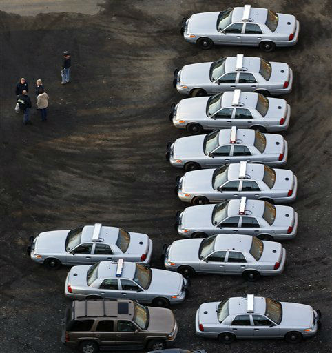 Police vehicles are lined up near a triage near Sandy Hook Elementary School in Newtown, Conn., where authorities say a gunman opened fire inside an elementary school in a shooting that left 27 people dead, including 18 children, Friday, Dec. 14, 2012.   <span class=meta>(AP Photo&#47; Julio Cortez)</span>