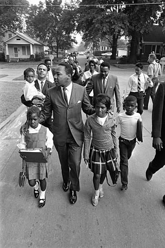 "<div class=""meta ""><span class=""caption-text "">Dr. Martin Luther King Jr. walks between seven-year-old Eva Gracelemon, left, and 10-year-old Aritha Willis as he escorts black school children to formerly all-white schools in Grenada, Miss., Tuesday morning, Sept. 20, 1966.  Violence erupted at the school last Monday when the schools were integrated. (AP Photo) (AP Photo/ XNBG)</span></div>"