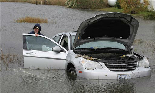 Glenn Heartley works on his car in a creek in Chincoteague, Va., Tuesday, Oct. 30, 2012. Heartley and his wife were swept off the road into a shallow creek when superstorm Sandy struck the area Monday.   <span class=meta>(AP Photo&#47; Steve Helber)</span>