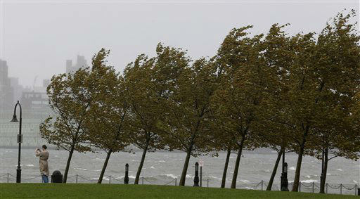 A person takes a photograph of the Hudson River as gusty winds bend trees, Monday, Oct. 29, 2012, in Hoboken, N.J. Hurricane Sandy continued on its path Monday, as the storm forced the shutdown of mass transit, schools and financial markets, sending coastal residents fleeing, and threatening a dangerous mix of high winds and soaking rain. &#40;AP Photo&#47;Julio Cortez&#41; <span class=meta>(AP Photo&#47; Julio Cortez)</span>