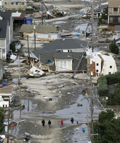 "<div class=""meta ""><span class=""caption-text "">In this aerial photo, people walk amid the destruction left in the wake of superstorm Sandy, Wednesday, Oct. 31, 2012, in Seaside Heights, N.J.   (AP Photo/ Mike Groll)</span></div>"
