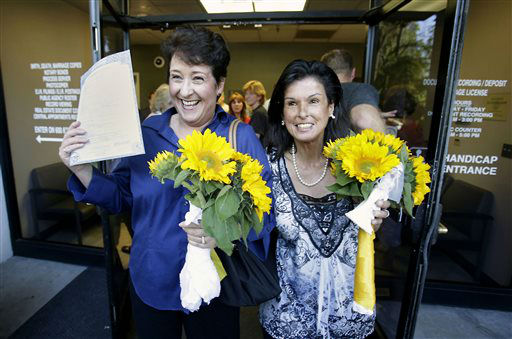Nicola Simmersbach, left, displays a marriage license as she Diana Luiz, leaves the Sacramento County Recorder&#39;s office after they got married in Friday, June 28, 2013.  in Sacramento, Calif.  A three-judge panel of the 9th U.S. Circuit Court of Appeals issued a brief order Friday afternoon dissolving, &#34;effective immediately,&#34; a stay it imposed on gay marriages while the lawsuit challenging the ban advanced through the court.  The couple had been engaged for five years and rushed to the recorders office where they became the first same-sex couple to get be married in Sacramento County after the ruling. <span class=meta>(AP Photo&#47; Rich Pedroncelli)</span>