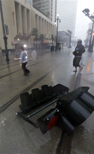 "<div class=""meta image-caption""><div class=""origin-logo origin-image ""><span></span></div><span class=""caption-text"">Pedestrians pass a fallen traffic light as Hurricane Isaac makes landfall, Wednesday, Aug. 29, 2012, in New Orleans, La. Isaac was packing 80 mph winds, making it a Category 1 hurricane. It came ashore early Tuesday near the mouth of the Mississippi River, driving a wall of water nearly 11 feet high inland and soaking a neck of land that stretches into the Gulf. The storm stalled for several hours before resuming a slow trek inland, and forecasters said that was in keeping with the its erratic history. The slow motion over land means Isaac could be a major soaker, dumping up to 20 inches of rain in some areas.   (AP Photo/ Eric Gay)</span></div>"