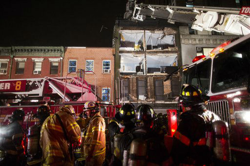 The facade of a four-story building on 14th Street and 8th Avenue collapsed onto the sidewalk as FDNY firefighters respond, Monday, Oct. 29, 2012, in New York. Hurricane Sandy bore down on the Eastern Seaboard&#39;s largest cities Monday, forcing the shutdown of mass transit, schools and financial markets, sending coastal residents fleeing, and threatening a dangerous mix of high winds, soaking rain and a surging wall of water up to 11 feet tall. &#40;AP Photo&#47; John Minchillo&#41; <span class=meta>(AP Photo&#47; John Minchillo)</span>