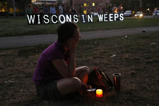 A woman sits with a candle during a vigil for the victims of the Sikh Temple of Wisconsin shooting, in Milwaukee, Sunday, Aug 5, 2012. An unidentified gunman killed six people at a Sikh temple in suburban Milwaukee in a rampage that left terrified congregants hiding in closets and others texting friends outside for help. The suspect was killed outside the temple in a shootout with police officers.   <span class=meta>(AP Photo&#47; JEFFREY PHELPS)</span>