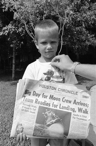 Mark Armstrong, six-year-old son of Apollo 11 Astronaut Neil Armstrong, picks up the morning paper at the family home near the Manned Spacecraft Center in Houston, Texas on July 20, 1969. Headlines proclaim the big day for all the world when his dad is scheduled to be the first man to set foot on the moon.   <span class=meta>(AP Photo&#47; Anonymous)</span>