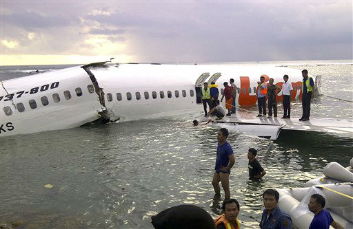 In this photo released by Indonesia&#39;s National Rescue Team, rescuers stand near the wreckage of a crashed Lion Air plane in Bali, Indonesia on Saturday, April 13, 2013. The plane carrying more than 100 passengers and crew overshot a runway on the Indonesian resort island of Bali on Saturday and crashed into the sea, injuring nearly two dozen people, officials said.   <span class=meta>(AP Photo&#47; Uncredited)</span>