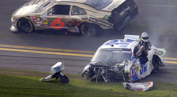 Driver Kyle Larson climbs out of his car as Trevor Bayne &#40;7&#41; rolls past after a crash at the conclusion of the NASCAR Nationwide Series auto race Saturday, Feb. 23, 2013, at Daytona International Speedway in Daytona Beach, Fla. &#40;AP Photo&#47;Chris O&#39;Meara&#41; <span class=meta>(AP Photo&#47; Chris O&#39;Meara)</span>