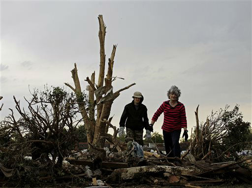 "<div class=""meta ""><span class=""caption-text "">Lea Bessinger and her son Josh Bessinger look through the rubble of the elder Bessinger's tornado-ravaged home Tuesday, May 21, 2013, in Moore, Okla. A huge tornado roared through the Oklahoma City suburb Monday, flattening an entire neighborhoods and destroying an elementary school with a direct blow as children and teachers huddled against winds.   (AP Photo/ Charlie Riedel)</span></div>"