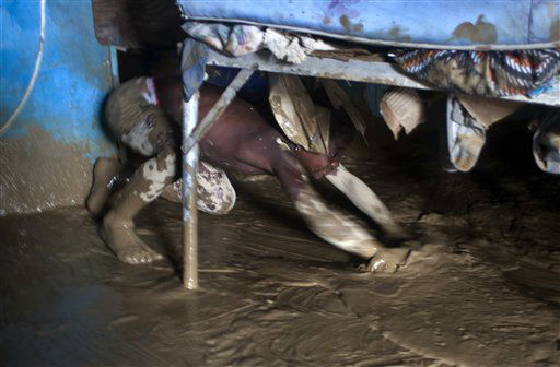 "<div class=""meta ""><span class=""caption-text "">A girl helps to drain mud from her flooded home after the passing of Tropical Storm Isaac in Port-au-Prince, Haiti, Sunday Aug. 26, 2012. The death toll in Haiti from Tropical Storm Isaac has climbed to seven after an initial report of four deaths, the Haitian government said Sunday. (AP Photo/Dieu Nalio Chery) (AP Photo/ Dieu Nalio Chery)</span></div>"