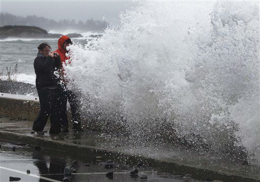 Lisa Famularo and her husband, Michael Green, prepare to get slammed by a large wave while making pictures of heavy surf in the Atlantic Ocean during the early stages of Hurricane Sandy, Monday, Oct. 29, 2012, in Kennebunk, Maine. Hurricane Sandy continued on its path Monday, as the storm forced the shutdown of mass transit, schools and financial markets, sending coastal residents fleeing, and threatening a dangerous mix of high winds and soaking rain.  <span class=meta>(AP Photo&#47; Robert F. Bukaty)</span>
