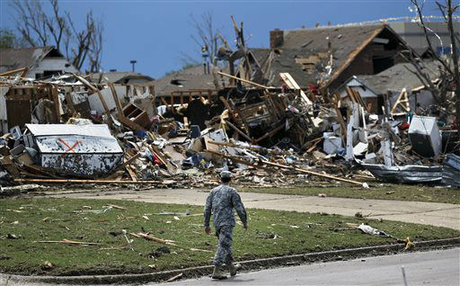 A soldier walks past the wreckage left when a tornado moved through Moore, Okla., Tuesday, May 21, 2013. The huge tornado roared through the Oklahoma City suburb, flattening entire neighborhoods and destroying an elementary school with a direct blow as children and teachers huddled against winds.   <span class=meta>(AP Photo&#47; Brennan Linsley)</span>