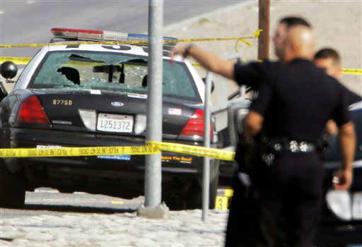 Police tape surrounds a bullet-damaged Los Angeles Police vehicle on Thursday Feb. 7, 2013 in Corona, Calif.  Former Los Angeles police officer Christopher Dorner is suspected if shooting at the two LAPD officers in the vehicle, who were sent to Corona to protect someone Dorner threatened in a rambling online manifesto. One officer&#39;s head was grazed by a bullet. Thousands of police officers throughout Southern California and Nevada hunted Thursday for Dorner, who was angry over his firing and began a deadly shooting rampage that he warned in an online posting would target those on the force who wronged him.   <span class=meta>(AP Photo&#47; Nick Ut)</span>
