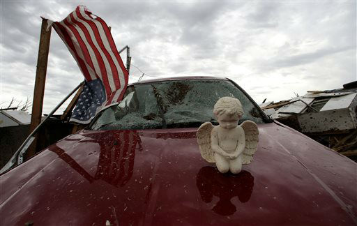 A concrete angel rests on a destropyed car in a tornado-ravaged neighborhood Tuesday, May 21, 2013, in Moore, Okla. A huge tornado roared through the Oklahoma City suburb Monday, flattening entire neighborhoods and destroying an elementary school with a direct blow as children and teachers huddled against winds.   <span class=meta>(AP Photo&#47; Charlie Riedel)</span>