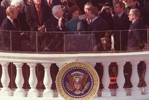Jimmy Carter takes the oath of office, as his wife, Rosalynn, holds the family bible, during the inauguration ceremony in January of 1977.  Administrating the oath is Chief Justice of the U.S. Warren Burger.  Looking on, from left, are: outgoing President Gerald Ford, and at right, Vice President Walter Mondale, and former Vice President Nelson Rockefeller.  <span class=meta>(AP Photo&#47; XMB PC)</span>