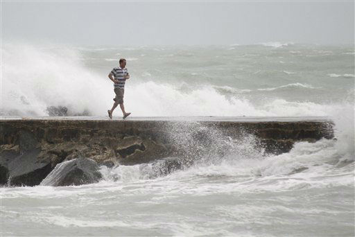 "<div class=""meta image-caption""><div class=""origin-logo origin-image ""><span></span></div><span class=""caption-text"">A man runs back from the end of a jetty as waves whipped up by Tropical Storm Isaac crash around him in Bal Harbour, Fla. Forecasters predicted Isaac would intensify into a Category 1 hurricane later Monday or Tuesday with top sustained winds of between 74 and 95 mph. The center of its projected path took Isaac directly toward New Orleans on Wednesday, but hurricane warnings extended across some 330 miles from Morgan City, La., to Destin, Fla. It could become the first hurricane to hit the Gulf Coast since 2008.   (AP Photo/ Wilfredo Lee)</span></div>"