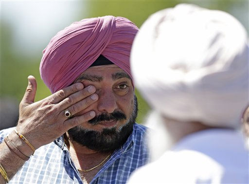 A man wipes away tears outside the Sikh Temple in Oak Creek, Wis. where a shooting took place on Sunday, Aug 5, 2012.   <span class=meta>(AP Photo&#47; Jeffrey Phelps)</span>