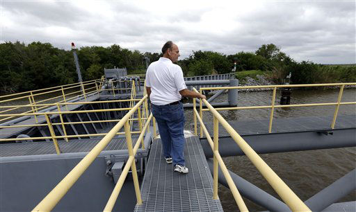 "<div class=""meta ""><span class=""caption-text "">Reggie Dupre, executive director of the Terrebonne Levee & Conservation District, checks on a flood gate as Isaac approaches Tuesday, Aug. 28, 2012, near Dulac, La. Isaac is churning it's way across the Gulf of Mexico heading towards Louisiana. Forecasters at the National Hurricane Center warned that Isaac, especially if it strikes at high tide, could cause storm surges of up to 12 feet (3.6 meters) along the coasts of southeast Louisiana and Mississippi and up to 6 feet (1.8 meters) as far away as the Florida Panhandle.  (AP Photo/ David J. Phillip)</span></div>"