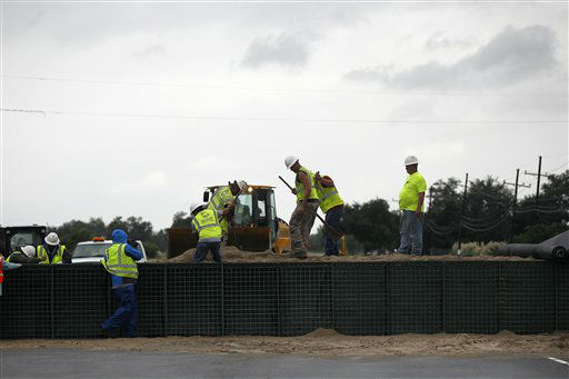 "<div class=""meta ""><span class=""caption-text "">Workers fill Hesco baskets at a flood wall at Route 23, in advance of Tropical Storm Isaac in Plaquemines Parish, La.,  Tuesday, Aug. 28, 2012. Forecasters at the National Hurricane Center warned that Isaac, especially if it strikes at high tide, could cause storm surges of up to 12 feet (3.6 meters) along the coasts of southeast Louisiana and Mississippi and up to 6 feet (1.8 meters) as far away as the Florida Panhandle.  (AP Photo/ Gerald Herbert)</span></div>"