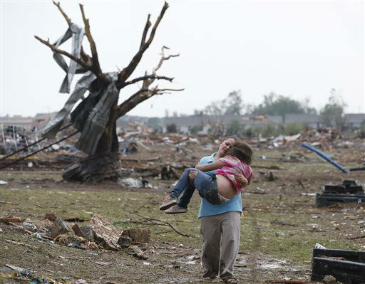 "<div class=""meta ""><span class=""caption-text "">A woman carries her child through a field near the collapsed Plaza Towers Elementary School in Moore, Okla., Monday, May 20, 2013. (AP Photo Sue Ogrocki) (AP Photo/ Sue Ogrocki)</span></div>"